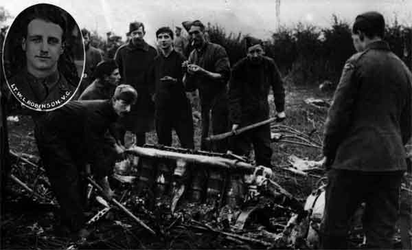 PC73/104/31: This image shows RFC personnel at the crash site of SL11 a few hours after its destruction.  One of the airship's Maybach engines can be seen in the centre, while inset is a portrait of Robinson.