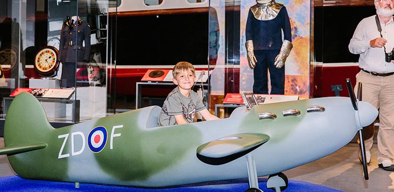Boy sitting in a model Spitfire aeroplane in H1
