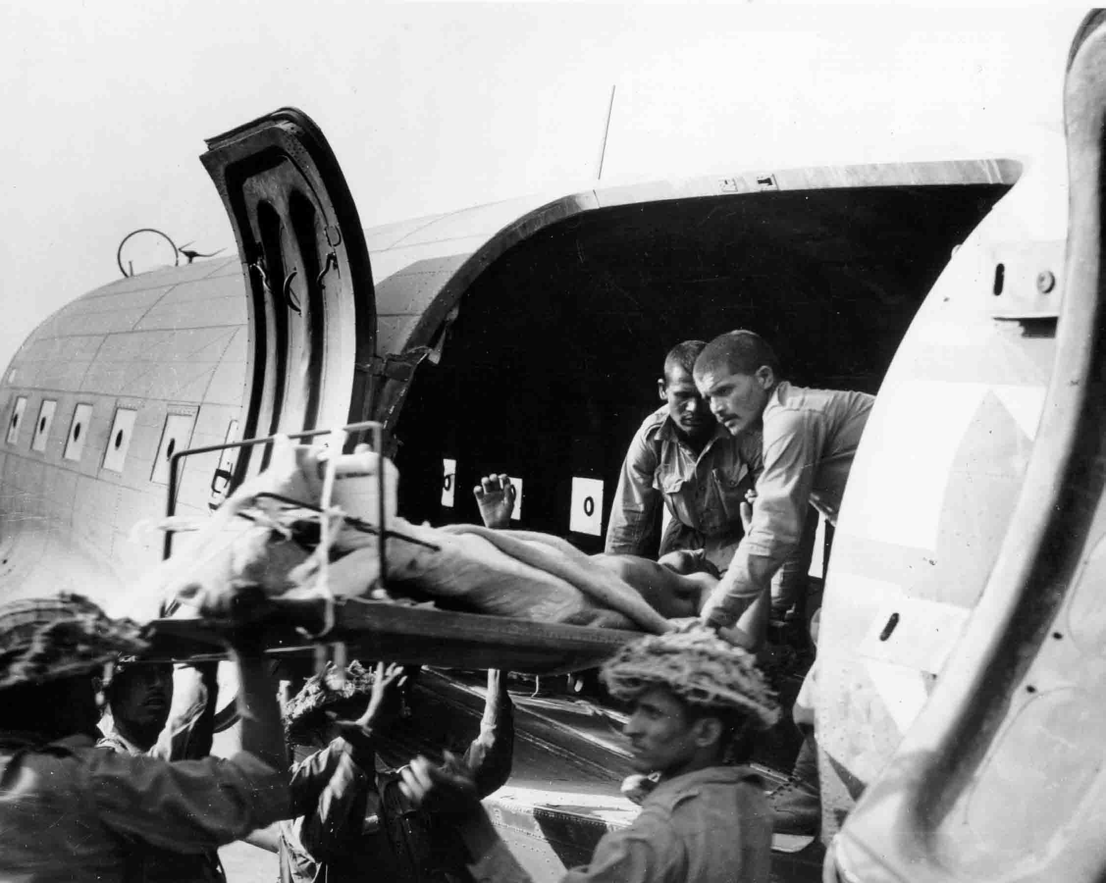 Stretcher-bearers carefully lift seriously wounded out of a USAAF C-47 of the 1st Air Commando Group, Burma, 1944 (RAFM PC71/19/1540)