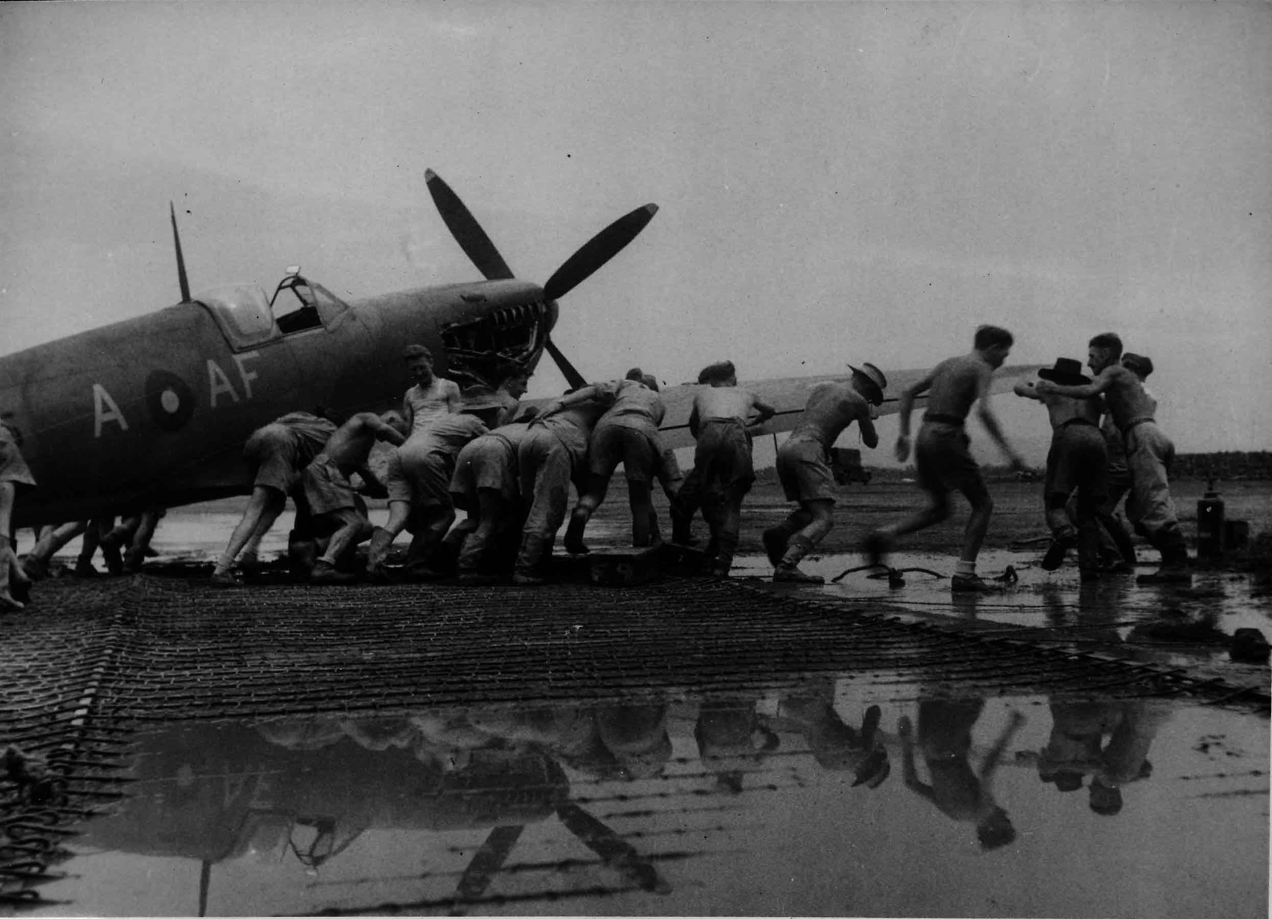 Manhandling a Supermarine Spitfire Mk VIII AF-A of No. 607 'County of Durham' Squadron through the monsoon mud at an advanced airfield on the Burmese border, 1944 (RAFM PC71/19/1742)