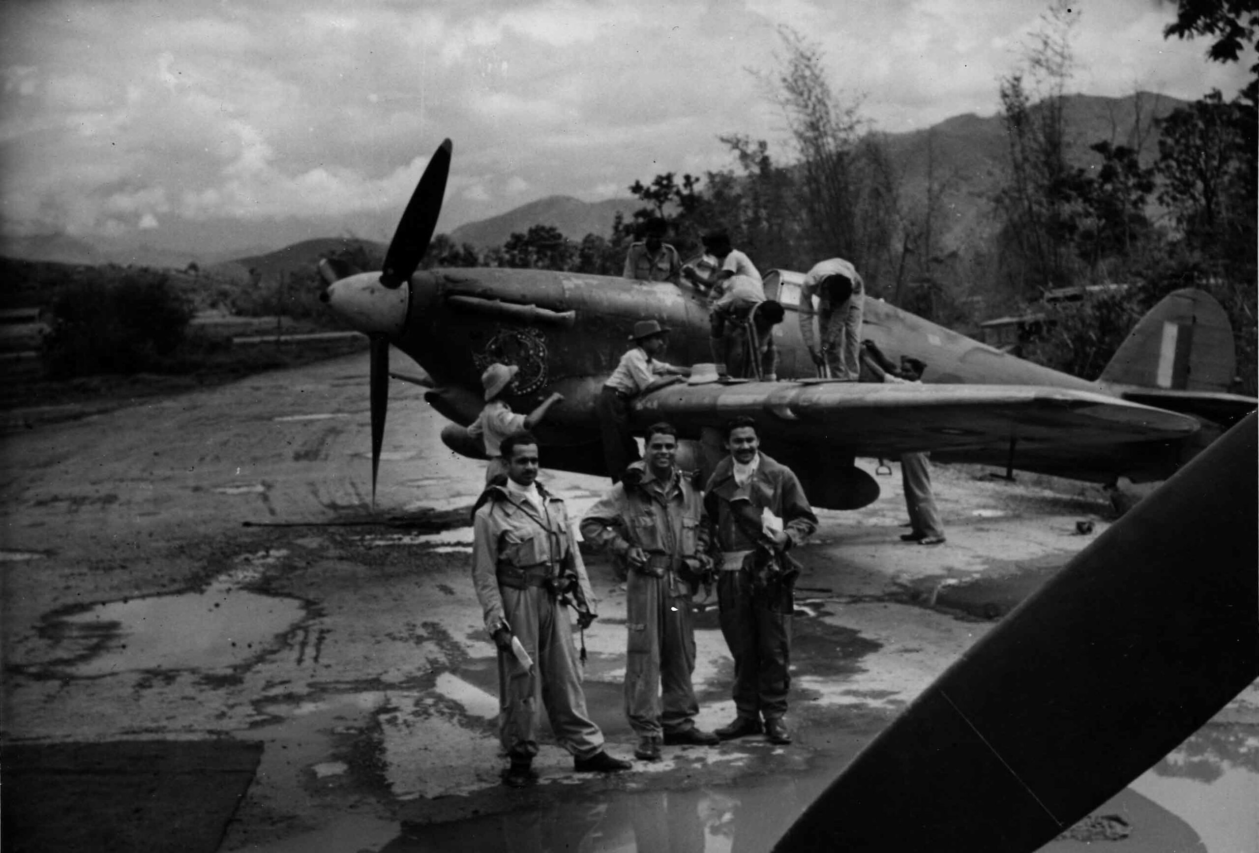 Indian Air Force pilots standing in front of a Hurricane as ground crew clean the canopy and re-arm the aircraft, 1944 (RAFM PC71/19/1754)