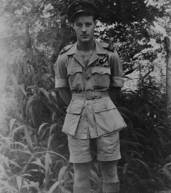 Flt Lt John Alan Quinton GC standing next to a tropical tree line
