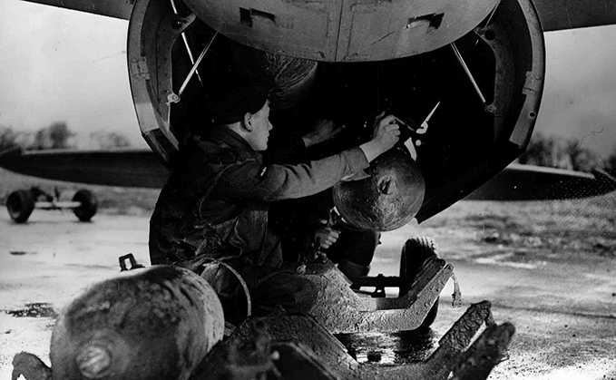 A photograph of a Mosquito FB VI being loaded with bombs by the armourer