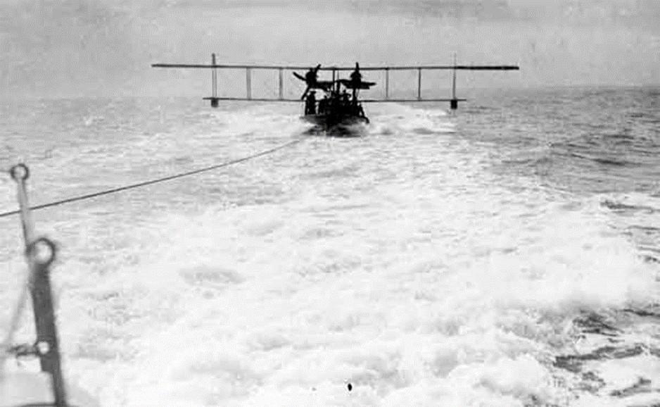 A lighter with a Curtiss H12 Large America on board being towed at speed behind a destroyer (RAFM reference: X003-2602/6551)