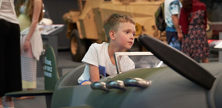 Close up of a boy sitting in a model Spitfire aeroplane in H1