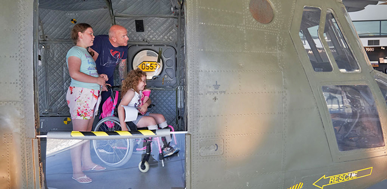 Family with child in a wheelchair in the back of the Chinook in H6