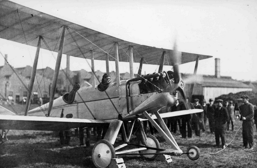 Bi-plane taking off with pilot in cap and googles.