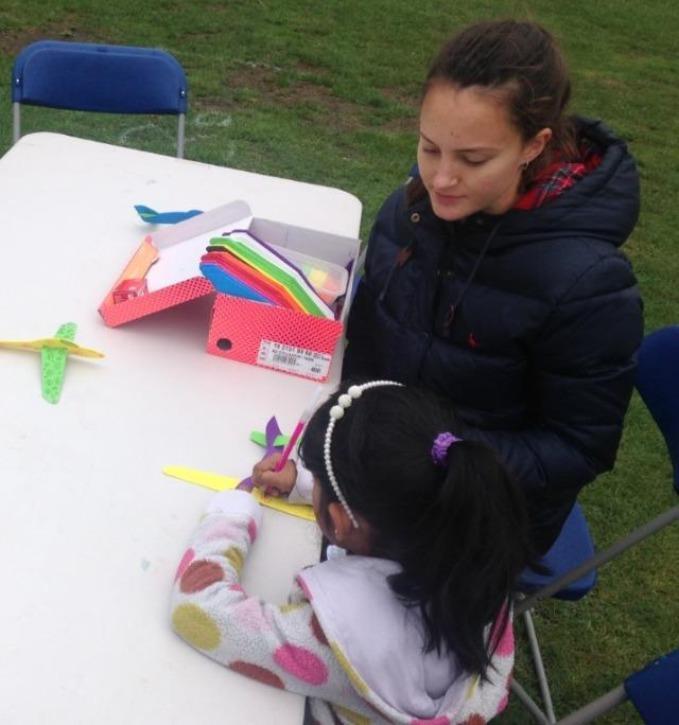 A Volunteer helping a girl make a foam plane