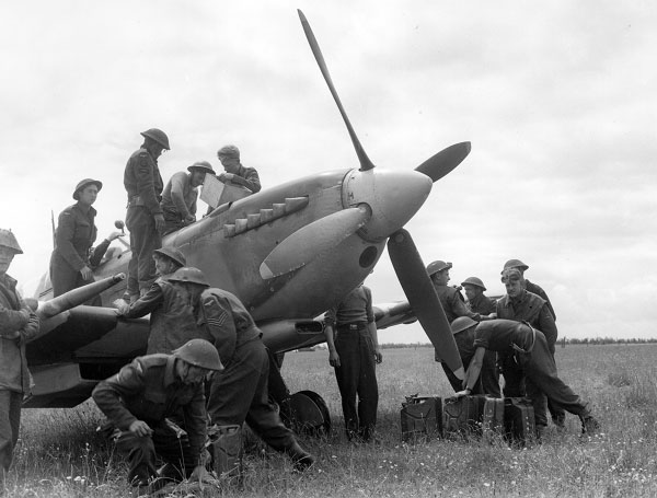RAF Servicing Commandos preparing to refuel and rearm a Spitfire in Normandy