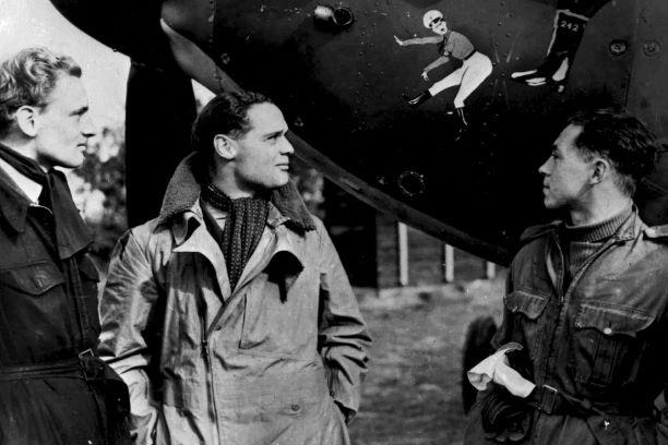 Figure 4: PC94/131/23 McKnight with Bader looking at cartoon on Bader's Hurricane and which was painted on most aircraft in No. 242 Squadron. McKnight is on the far right. Royal Air Force Museum Collection.