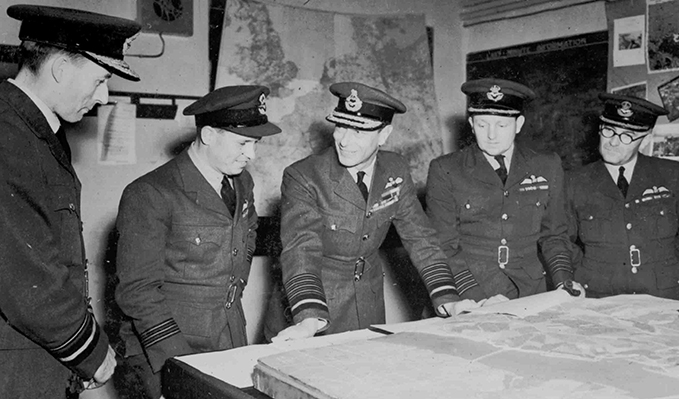 HM King George VI looking at a model of one of the dams. To his right are Wing Commander Guy Gibson and to his right, Group Captain Whitworth