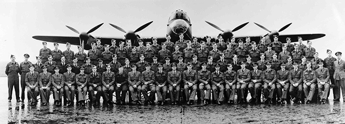 Formal group photograph of the air crew of 617 Squadron posing in front of an Avro Lancaster