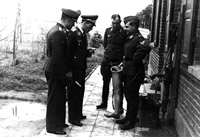 Luftwaffe personnel examine one of Bader's legs - presumably the spare leg dropped by parachute to replace his damaged leg.