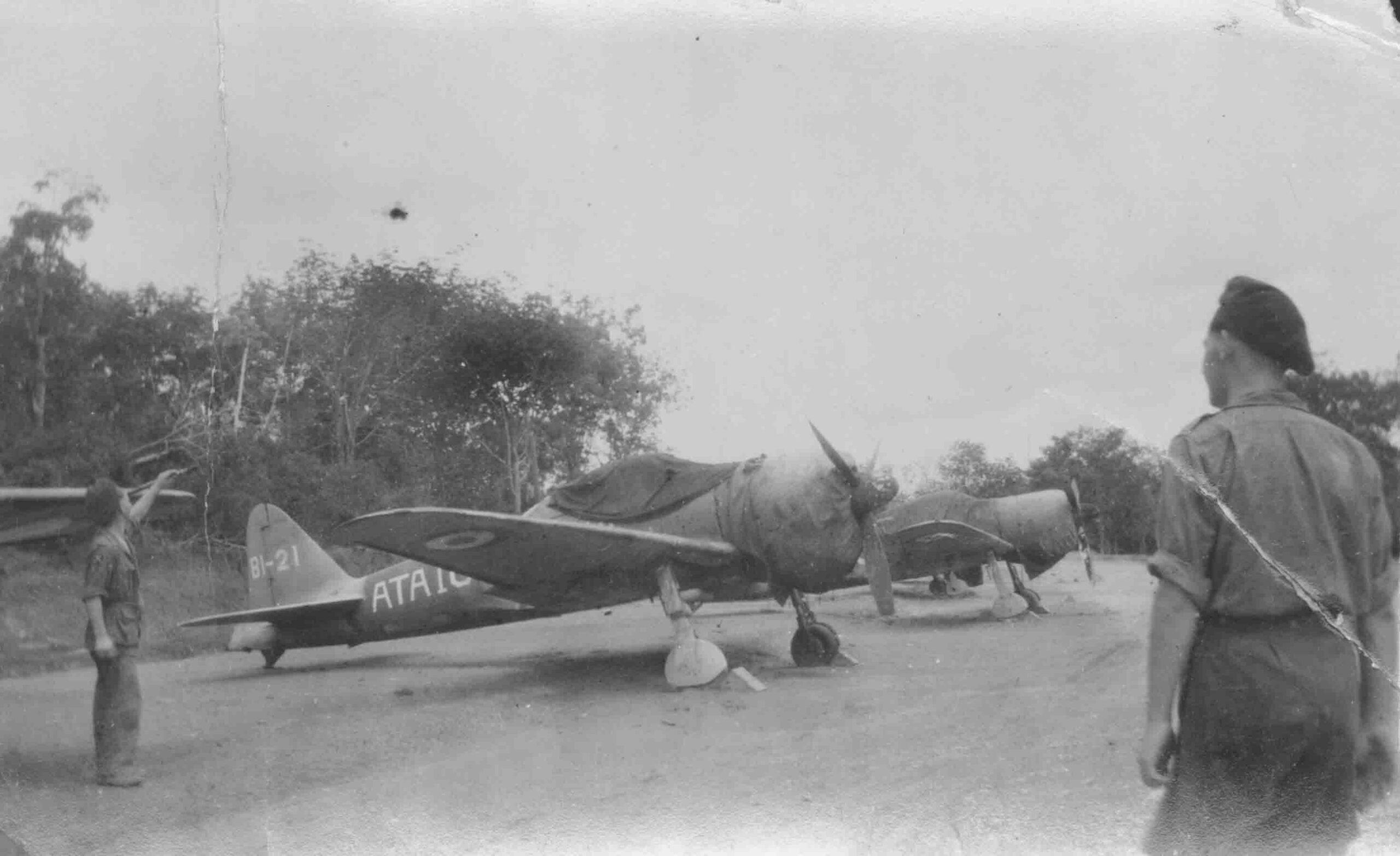 PC97/112/1s Two airmen near line up of  captured Zeros in RAF markings. Malaya, 1946