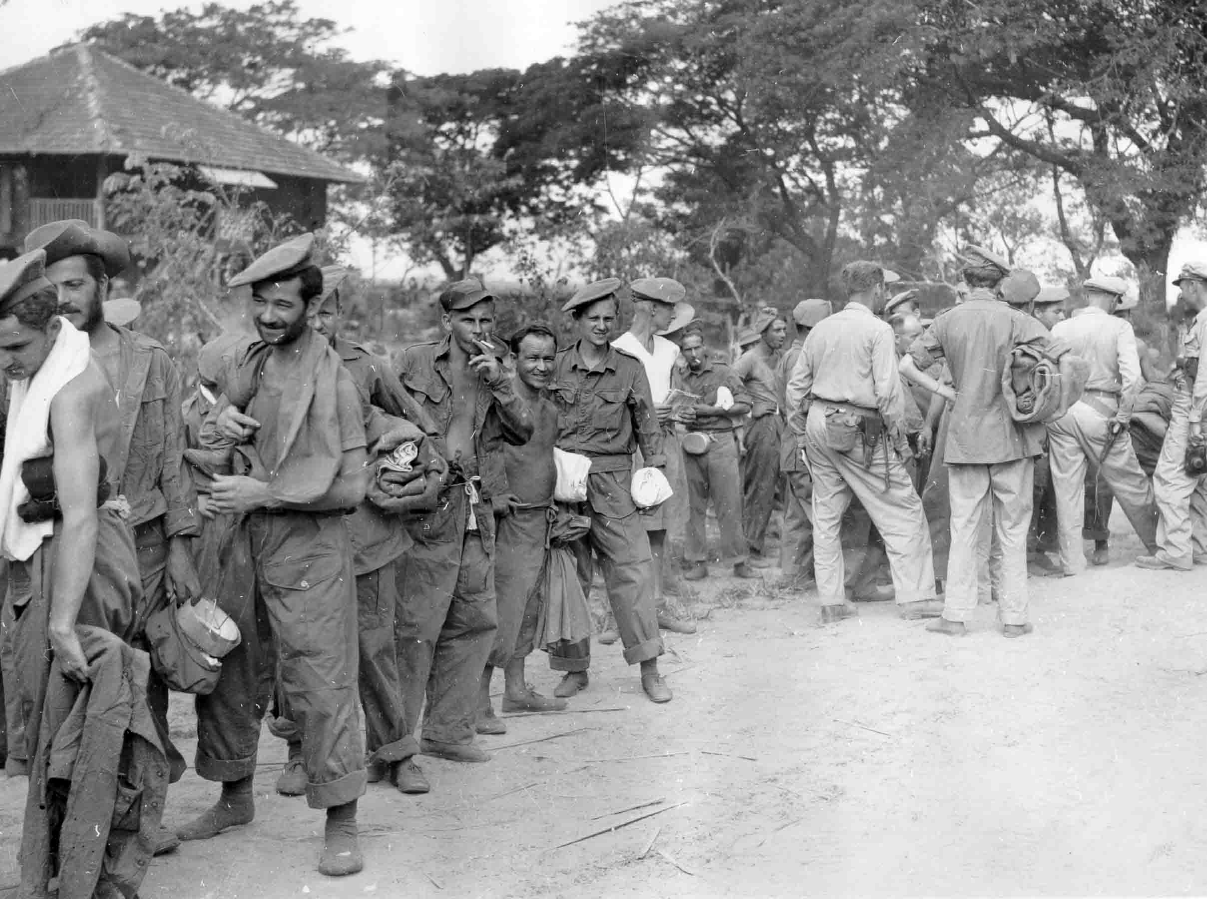 Liberated British and American PoWs waiting at an airfield to be taken to Calcutta after release from Japanese PoW camp, Burma, 1945 (PC71_19_1508)