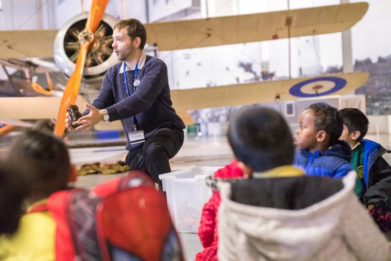 Staff member talking to school children in front of a First World War aeroplane