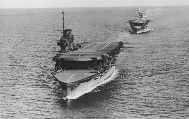 P013873: HMS Glorious, Furious and Courageous seen in line astern, 1934.  The unusual deck, the forward section of which sloped upwards towards the bow, can be discerned on both Glorious and Furious.  This feature aided the stopping of aircraft after landing.  The secondary flying-off deck, below the main deck, can also be seen on all three ships.  Interestingly, the Japanese Akagi, an approximate contemporary, featured three flying decks, the uppermost of which sloped from amidships towards the bow and stern, to assist the take-off and stopping of aircraft.  A participant in the attack on Pearl Harbor, she was badly damaged at the Battle of Midway in 1942 and eventually scuttled.