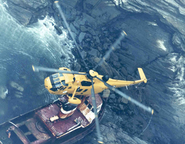 The Museum's Westland Sea King HAR.3 (XZ585) of 202 Squadron, front port above view hovering over ship aground, Devil's Point, 1984
