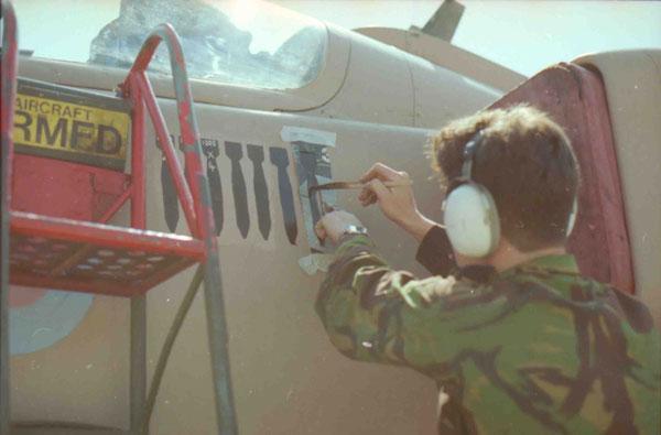 SAC John Podmore painting a bomb symbol on the nose of Sepecat Jaguar GR.1A (XZ119 'Katrina Jane'), Muharraq, 15 February 1991 (P031537)