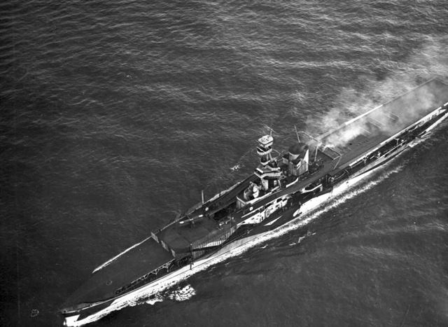 PC73/82/177: HMS Furious in the Firth of Forth, 1918.  The fore and aft decks can be seen in this aerial view, as well as the strips of connecting decking which led around the central superstructure.  The forward lift can be seen in the lowered position.