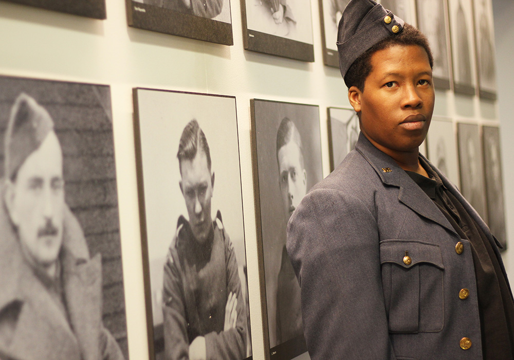 Staff member dressed in a short RAF jacket with an RAF cap on his head. He is standing by a wall of photos showing people who served during the First World War
