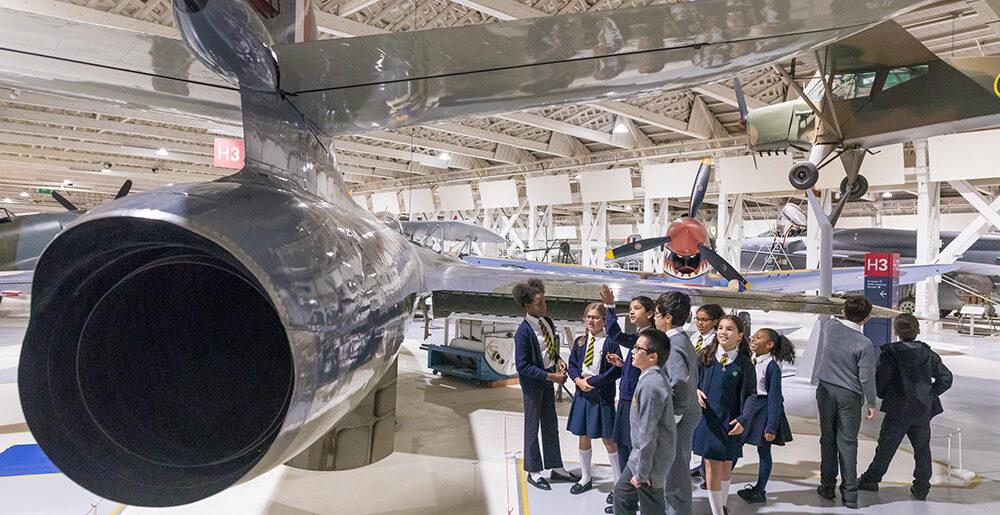 School children looking at a jet plane