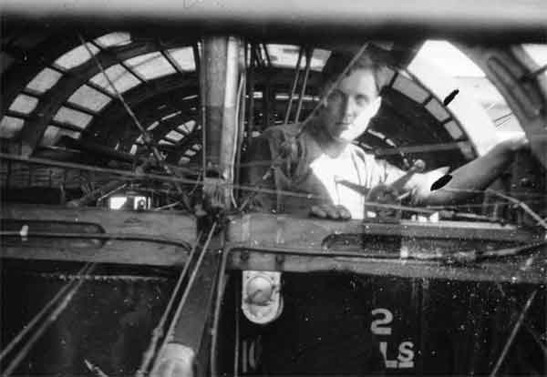 The engineer of a Felixstowe F.3 standing at his crew station inside the fuselage.  He is looking towards the cockpit.  (RAFM reference X003-2602-6876)