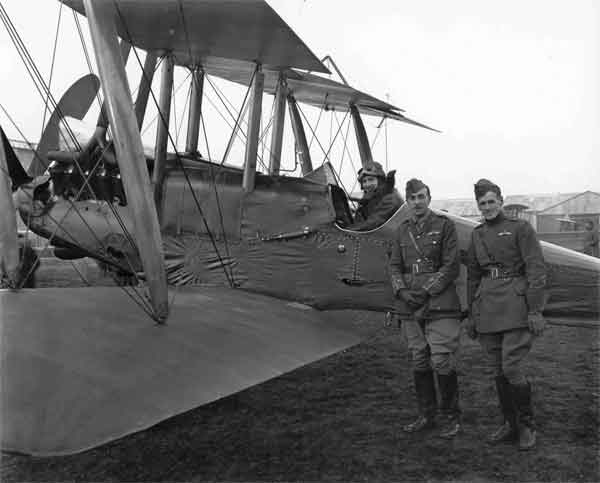 X003-2602/10465: A Daimler-built Royal Aircraft Factory B.E.12a, serial 6511, photographed at Farnborough in December 1916.  Captain William Leefe Robinson can be seen in the cockpit with Major Frank Goodden (left) and Lt P F W Bush standing in front.  The aircraft was fitted with modified wings incorporating widely-raked tips and horn-balanced ailerons.