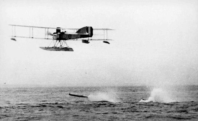 X003-2602/12966: The same aircraft begins to climb away as the torpedo appears to skip across the water's surface.