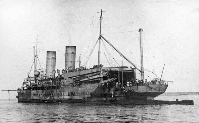 X003-2602/13055: Short Admiralty Type 184, serial 842, suspended from the crane of HMS Ben-My-Chree in the Dardanelles during 1915.  An E Class submarine is visible in the foreground.  Although small-scale operations were possible with floatplane tenders, it was obvious that vessels with flying-off decks were needed.