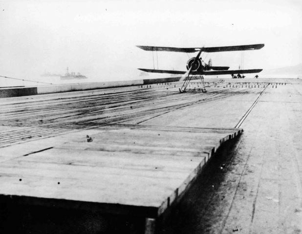 X003-2602/14339: A Beardmore-built Type 9901a Pup lands aboard HMS Furious, 1918.  This aircraft is equipped with a skid undercarriage and is being arrested by the longitudinal cables.