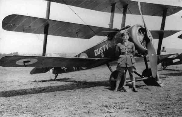 """X003-2602/14670: Sopwith Triplane, serial N6301, """"Dusty II"""", RNAS, 1917.  The Triplane's pilot, Flt Cdr Roderick McDonald, is standing in front.  Another instance of an affectionately-named naval aircraft, this Triplane led an active life before being destroyed in a fire at Bailleul on the night of 1 October 1917.  A red band, outlined in white, was applied to the Triplane's fuselage."""
