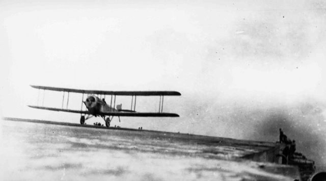 X003-2602/15912: A Sopwith Cuckoo landing aboard an aircraft carrier, probably HMS Eagle, probably 1920.