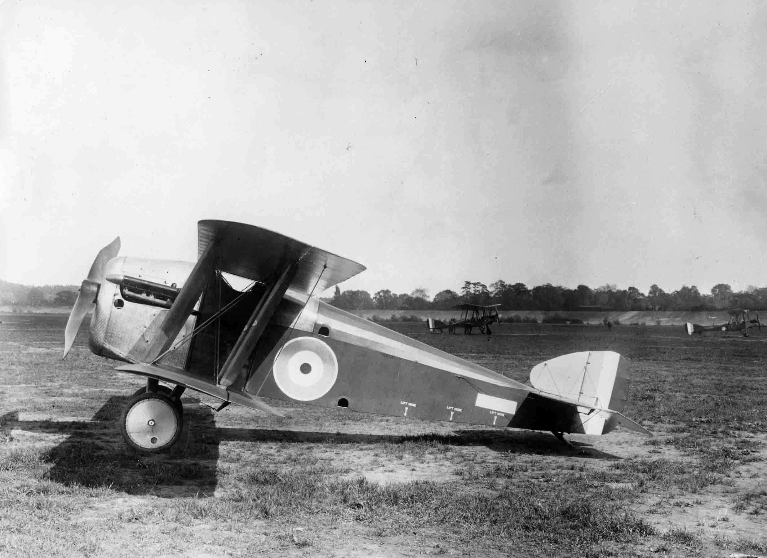 X003-2602/15935: Sopwith 5F.1 Dolphin, first prototype, at Brooklands, May 1917.  The distinctive appearance of the aircraft can be readily appreciated in this view.  At this stage, the aircraft was in its original form with the initial version of fuselage decking and there were no cooling vents in the engine cowling.  Two B.E.2es were in the background.