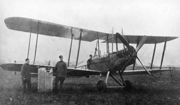 X003-2602-9668: Royal Aircraft Factory B.E.2c, serial 2693, with Lt Robinson sitting in the cockpit, B Flight, 39 Squadron, RFC, Suttons Farm, early September 1916. This is a rare photograph of Robinson's aircraft, as it was destroyed by fire following a crash at Suttons Farm on 16 September.  The two airmen to the left are holding the upper wing centre section, damaged by Robinson's Lewis gun during the attack on SL11. It may be noted that the Lewis gun is fixed to a Strange Mounting and that navigation lights and flare brackets are attached to the lower wing.  The forward fuselage appears to have been camouflaged, probably in PC10.