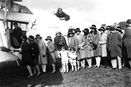 Sir Alan Cobham in the cockpit of his de Havilland D.H.61 biplane with a line of children waiting for their free flight
