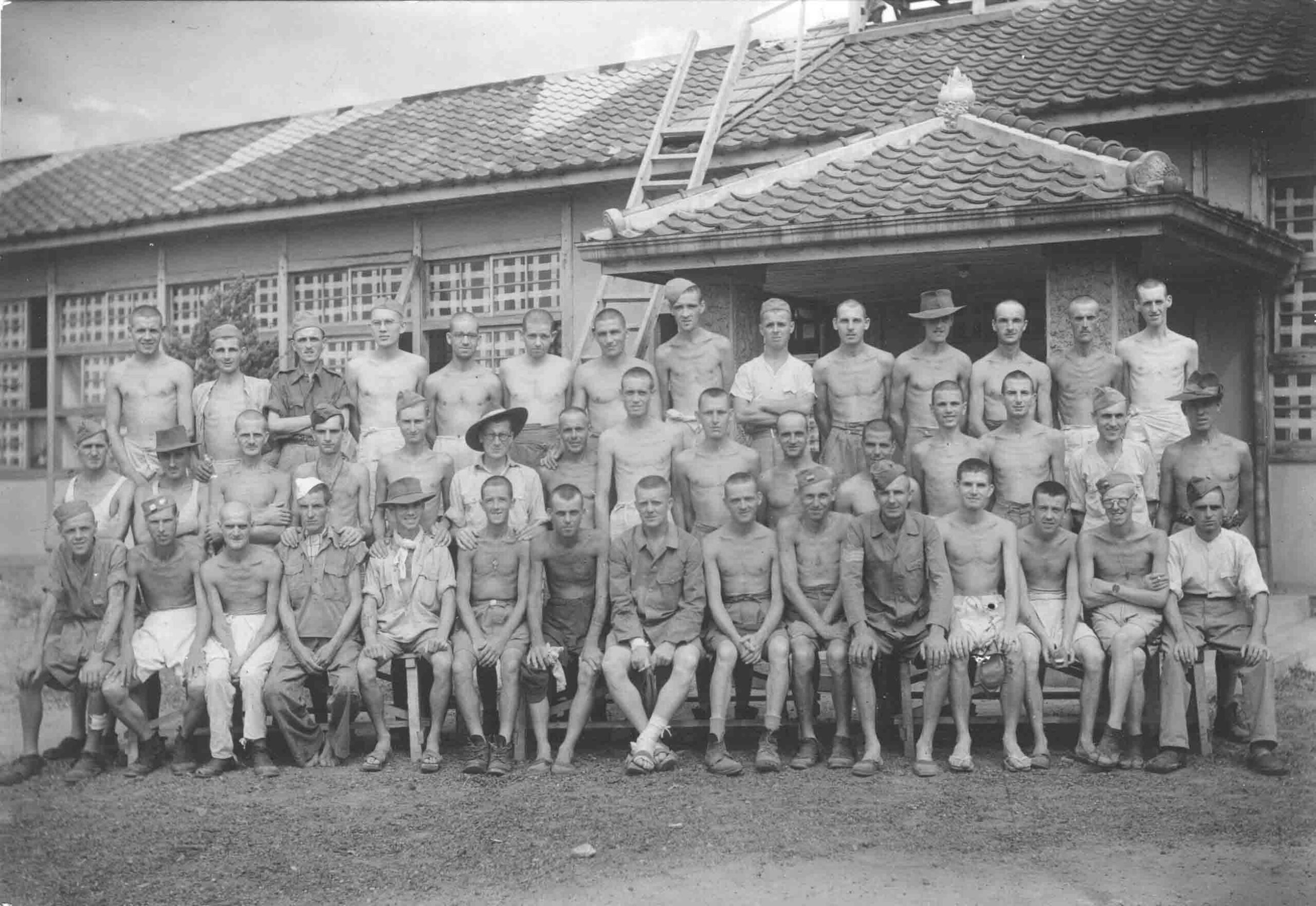 X001-3829/002/010  Group of Australian and British prisoners of war posing in front of the main prisoner of war camp building, Japan 1945.