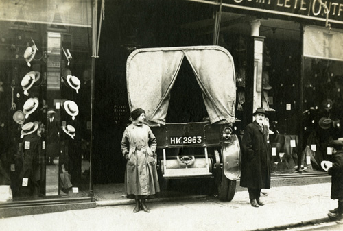 A WRAF stands by her vehicle which has crashed into a shop window