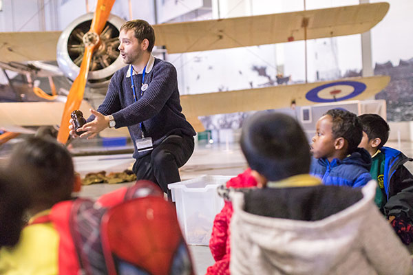 Member of London's Access and Learning Team talking to children in Hangar 2