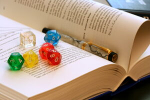 An image of an open book with a pen and coloured dice placed on top of a page.