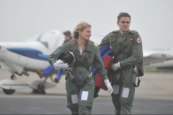 Two people walking away from an aeroplane