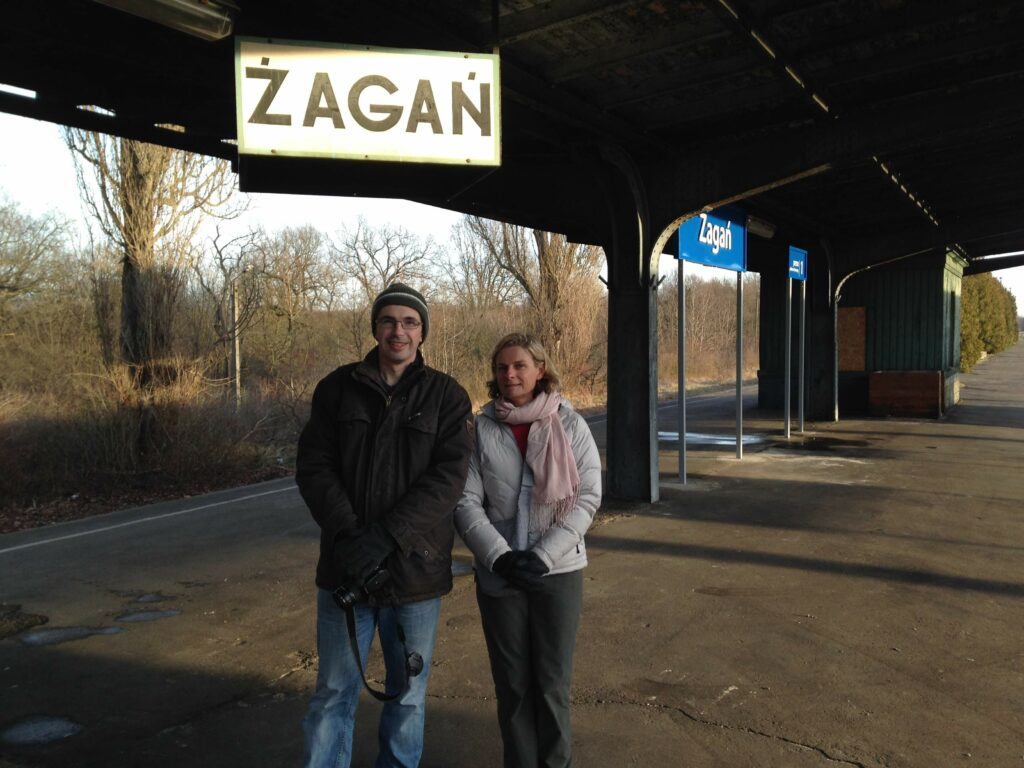 A man and woman standing beneath the railway sign for Sagan