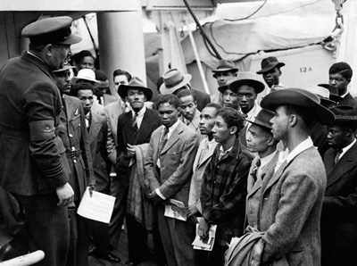 Airmen and veterans on board HMT Empire Windrush being welcomed by RAF officials from the Colonial Office, Tilbury, 21-22 June 1948 (Courtesy of Press Association Archive) Flight Lieutenant Johnny Smythe from Sierra Leone is standing second from left and Jamaican Sam King MBE is back row, far right.