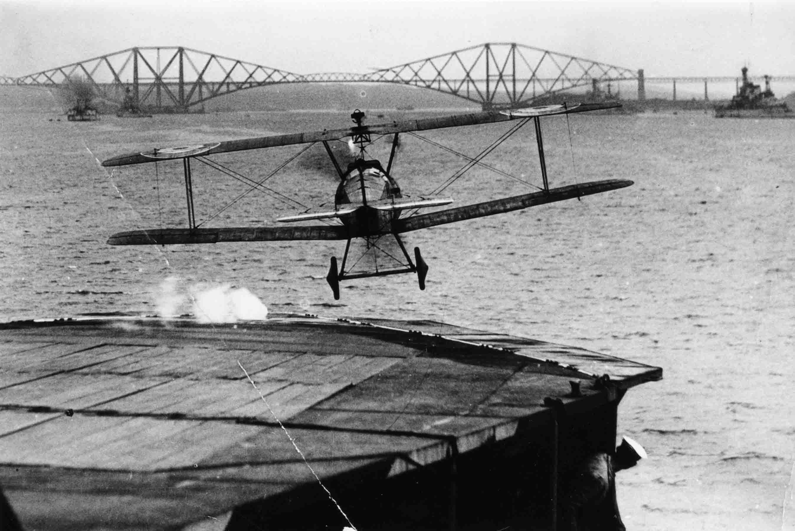 X003-2602/15784: Sopwith 2F.1 Camel during taking off from an early carrier, probably HMS Pegasus, in the Firth of Forth, probably during 1918.