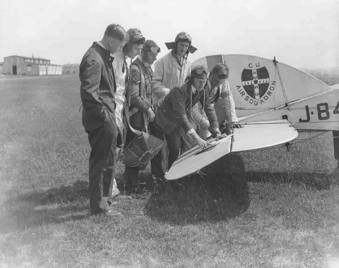 Six aircrew plotting flight on a map on the tail of a Cambridge University Air Squadron Bristol F2b Fighter