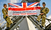 Two Army Personnel with an Armed Forces Day Flag