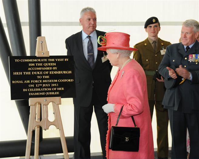 The Queen unveils a commemorative plaque, celebrating her visit to the Museum