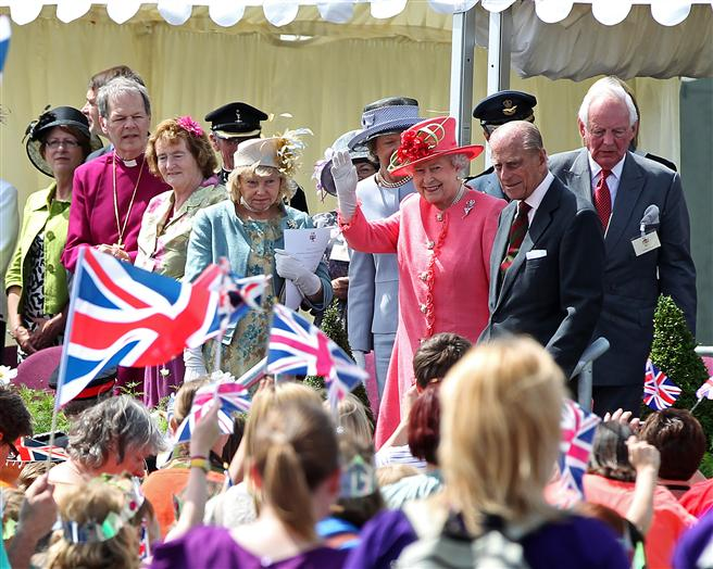 The Queen waves goodbye to the cheering crowds