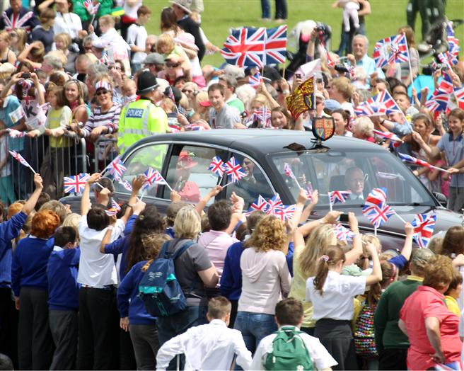 The Queen and Duke are driven through the cheering crowds at Cosford