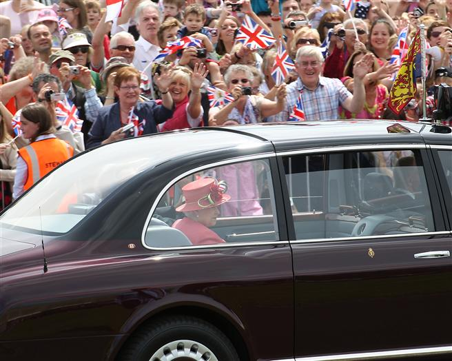 Crowds cheer as the Queen and Duke drive past